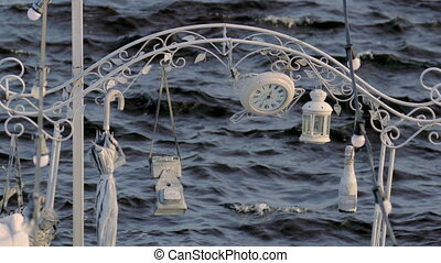 beautiful wedding decoration hanging on the arch at the background of the water and sway in the wind.
