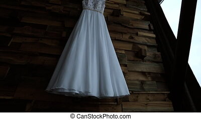 Beautiful wedding dress are hung on hanger in art studio.