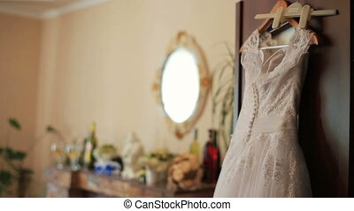 Beautiful wedding dress ready for bride hanging in the luxury apartments