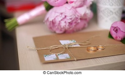 Beautiful wedding rings lie on the envelope against the...