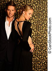 Beautiful well-dressed couple standing against abstract wall