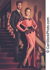 Beautiful well-dressed young couple standing on a steps in luxury interior
