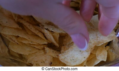 Beautiful well-groomed hands of the women take potato chips....