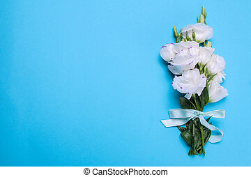 Beautiful white bouquet of flowers eustoma on a bright blue background top view with a place for an inscription