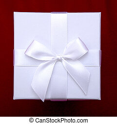 beautiful white gift box with ribbon on top of red sofa background