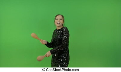 Beautiful white girl in a black shiny dress. Have fun and dance with maracas. On a green background.