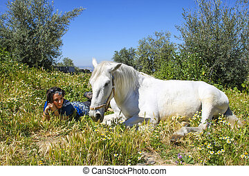 Beautiful white horse with a young woman at his side among the f