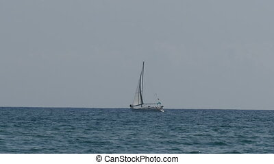 Beautiful white sailboat on the horizon, floating on a sea -...