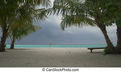 Beautiful white sand beach in Maldives. Storm at sea against...