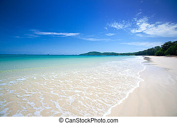 Beautiful white sandy beach with crystal clear blue water and blue sky