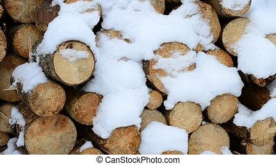 Beautiful white snow falling gently on background of wooden logs