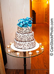 beautiful white three-tier cake with a turquoise bow on top is on the table.