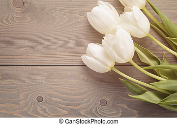 beautiful white tulips on wooden background with copy space