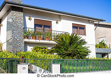 Beautiful white villa with garden and fence in Portugal. Exterior of modern residence.
