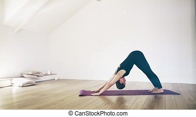 Beautiful white woman doing yoga indoors, side view