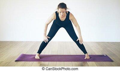 Beautiful white woman doing yoga inside, front view