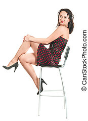 Beautiful white woman in dress on armchair. Long hair. Studio shot. White background, isolated