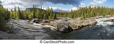 Beautiful wide panoramic landscape with wild glacier river Kamajokk, boulders and spruce tree forest in Kvikkjokk in Swedish Lapland. Summer sunny day, golden hour, dramatic clouds.