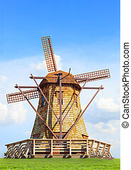 beautiful wind mills on green grass field against natural blue sky