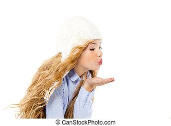 beautiful winter kid girl blowing wind with lips