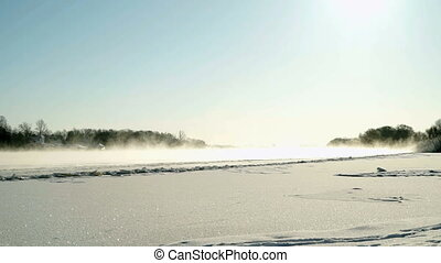 Beautiful winter landscape in sunny day. Water vapor on...