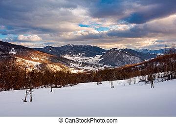 beautiful winter landscape of Carpathians. Village down in...