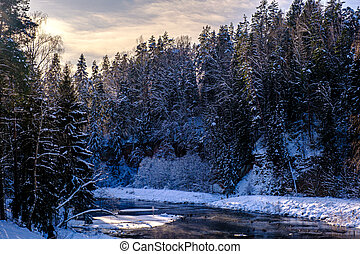 beautiful winter landscape. Snow-covered banks of a small river in the winter forest at dawn.