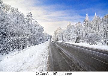winter landscape with asphalt road, forest and blue sky
