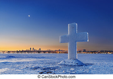 Beautiful winter landscape with Ice Cross on frozen river at Dusk