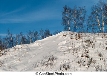 Beautiful winter landscape with snow-covered hills at sunset