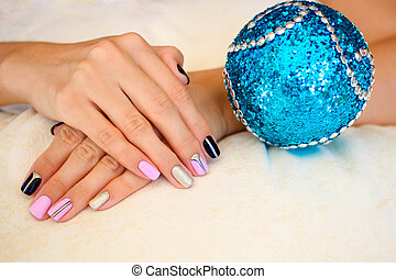 Beautiful winter manicure lacquer on new year balls .