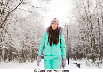 Beautiful winter portrait of young woman in the snowy nature