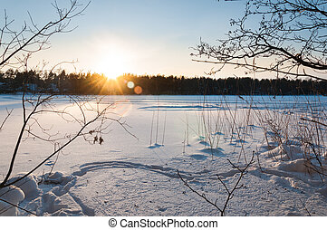 Beautiful winter scene. Sunset at the frozen lake covered with snow.