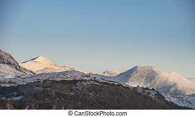 Beautiful Winter sunrise landscape image of Mount Snowdon and other peaks in Snowdonia National Park