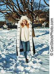 Beautiful winter woman in fur coat having fun outdoor