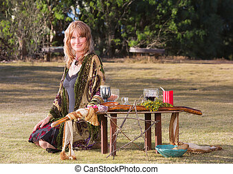 Beautiful Witch with Altar - Beautiful female witch sitting...
