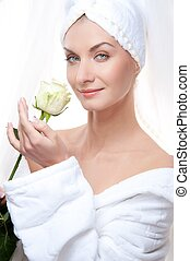 Beautiful woman after shower holding a white rose.