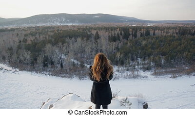 Beautiful woman against background of snow covered nature, rear view