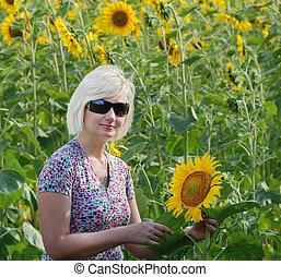 Beautiful woman alone among sunflow