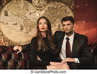 Beautiful woman and handsome young man sitting on a sofa in luxury interior