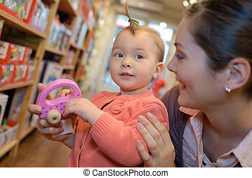 beautiful woman and her baby playing in toy store