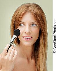 beautiful woman applying blush with brush