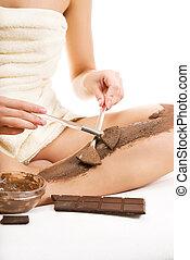 Beautiful woman applying chocolate mask to her skin
