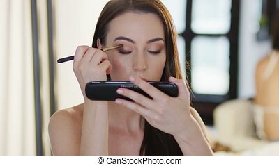 Beautiful woman applying cosmetics