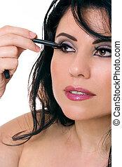 Beautiful woman applying eye pencil