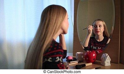 Beautiful woman applying eyebrow makeup