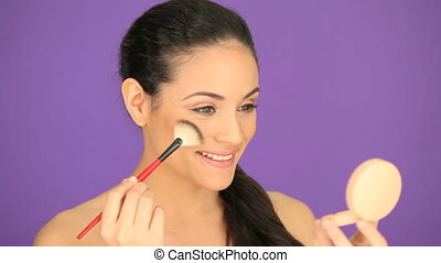 Beautiful woman applying foundation