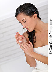 Beautiful woman applying hair conditioner