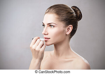Beautiful woman applying hygienic lip balm. Lipcare Stick....
