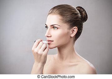 Beautiful woman applying hygienic lip balm. Lipcare Stick....